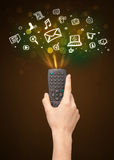 Hand with remote control and social media icons Royalty Free Stock Images