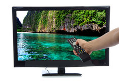 Hand with remote control turning on led tv. Hand with remote control turning on Plasma LED LCD TV with beautiful relax ocean water on screen isolated on a white Stock Image
