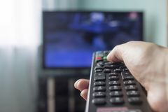 A hand with a remote control from the TV, in the background there is a TV button stock images