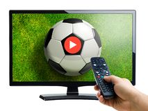 Hand remote controller pointing at football match video display Royalty Free Stock Images