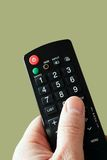 Hand with a remote in front. Of a green background Stock Images