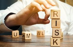 Hand removes blocks with the word Risk. The concept of reducing possible risks. Insurance, stability support. Financial pillow. royalty free stock photos