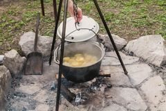 Hand removes lid from kettle over fire. We cook food at the stake. a tourist bowler weighs on a triple rack on a stone round platform. The hand removes the lid royalty free stock photos