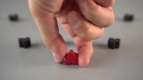 The hand removes the red figure from the environment of black figures. On a gray surface. The concept of the dismissal of the leader from the team stock video footage