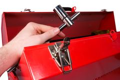 Hand removing a wrench from a toolbox. A hand removing a socket wrench from a red metal toolbox, isolated against white background Stock Photos