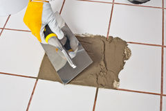 Hand Repaired old white tiles floor with Trowel Stock Photo