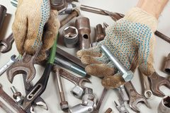 Hand of repairman in gloves with tools for repairing machines in workshop Royalty Free Stock Images