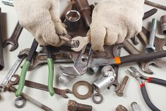 Hand of repairman in gloves with wrench to tighten the nut. Hand of repairman in gloves with a wrench to tighten the nut Stock Photo