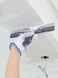 Hand repairs gypsum plasterboard frame. With spackling paste Stock Image