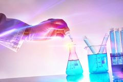 Hand of researcher with dropper and chemical containers with lights. Hand of researcher with dropper and chemical containers with blue liquid in the laboratory royalty free stock photos