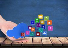 hand rest on a table with cloud over and application icons coming up form it. Blue wall behind Stock Photos