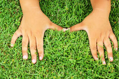 Hand resting on the grass. Stock Photo