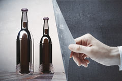 Hand revealing clear beer bottles. Hand flipping abstract concrete page revealing clear logo brown beer bottles on dark background. Mock up, 3D Rendering Royalty Free Stock Photography
