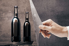 Hand Revealing Empty Beer Bottles Royalty Free Stock Photography