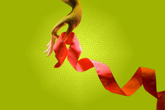 Hand with ribbon. Hand with red/orange ribbon, isolated on a green background royalty free stock images