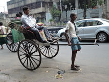 A hand rickshaw puller pulls a man in the middle of the road. Royalty Free Stock Image