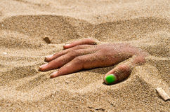 Hand in rigor mortis on the beach. On the beach hand in rigor mortis protruding from the sand Stock Images