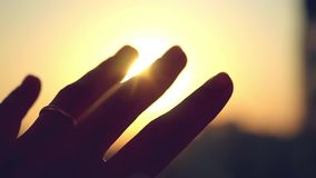 Hand with ring on finger of bride touch the sun on sunset city background in slowmotion. 1920x1080 stock video
