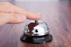 Hand ringing service bell kept on wooden table Royalty Free Stock Photography