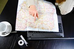 Hand on roadmap. Woman is sitting at cafe with laptop and pointing at road map, top view Stock Photos