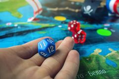 Hand rolls the blue dice on the world map of the playing field handmade Board games with a pirate ship. The game of battleship royalty free stock images