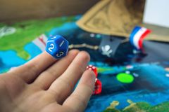 Hand rolls the blue dice on the world map of the playing field handmade Board games with a pirate ship. The game of battleship stock photo