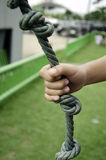 Hand rope. Child's hand holding a rope in the grass Stock Images