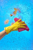Hand in rubber glove cleaning window on a blue sky background Stock Photo