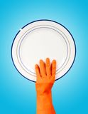 Hand in rubber glove holding clean plate Royalty Free Stock Image