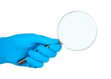 Hand in rubber glove holding magnifier. Royalty Free Stock Photos