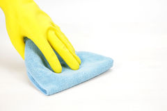 Hand with rubber glove wiping with a cloth Stock Images