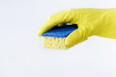 Hand in rubber yellow glove holding sponge on white background. cleaning Royalty Free Stock Images