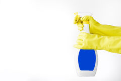 Hand in rubber yellow glove holds  spray bottle of liquid detergent on white background. cleaning Stock Images