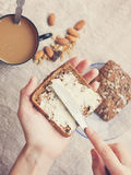 Hand  rubs butter on piece of rye bread Royalty Free Stock Image