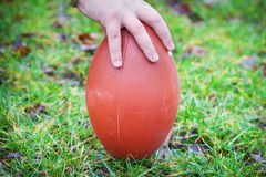 Hand on rugby ball. On green grass background royalty free stock photography