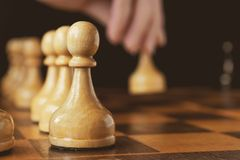 A hand`s of chess player makes a move the white pawn forward royalty free stock photos