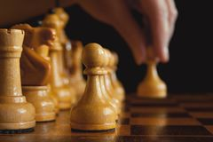 A hand`s of chess player makes a move the white pawn forward, ou Stock Photos