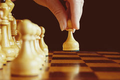 A hand`s of chess player makes a move the white pawn forward to Stock Image