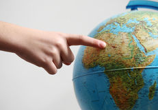 Hand's child pointing on a globe. Hand's child pointing africa on a globe stock photography