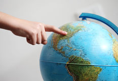 Hand's child pointing on a globe. Hand's child pointing usa on a globe stock photography