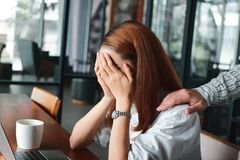 Hand`s of colleague comforting depressed sad Asian woman with hands on face crying on the workplace in office. Hand`s of colleague comforting depressed sad Royalty Free Stock Images