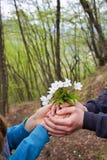 Hand s die van jongen een klein boeket van wilde witte bloemen aanbieden aan een meisje royalty-vrije stock afbeelding