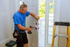 Hand & x27; s-mannen med skruvmejsel installerar dörrknoppen arkivfoton