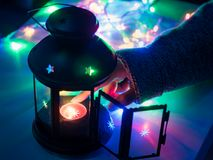 Hand of 25s to 35s girl with winter cloth arrange and lighting t. He red candle in black lantern in the night from christmas celebration event with soft focus Stock Photos