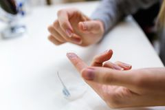 Hand`s of young woman holding one contact lenses before putting on them. Close-up of hand`s of young woman holding one contact lenses before putting on them royalty free stock photography