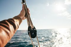 Hand of sailor holds onto rope in pulley. Sailor or tourist in windproof brown leather jacket holds on to rope or cord inside pulley, in nautical knot on a Stock Image