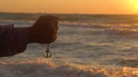 Hand of sailor man drops the anchor on chain with beautiful sunset above the black sea at background stock footage