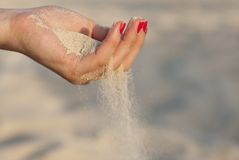 Hand with sand. Single woman hand with sand and red nails Stock Photography
