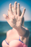 Hand in sand. Instagram stylisation. Woman show`s hand covered with sand on a blue sea background. Instagram stylisation Royalty Free Stock Image