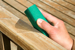 Hand with sandpaper. Removing  old tint from wooden surface with sandpaper Stock Photos